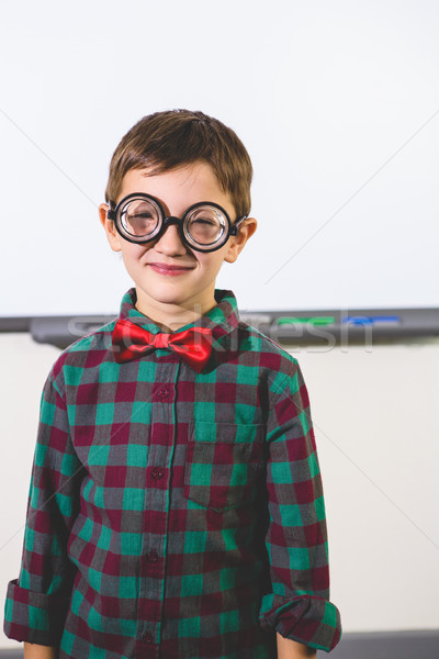 Smiling boy standing against whiteboard in classroom Stock photo © wavebreak_media