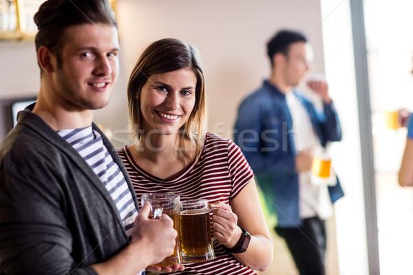 Happy young couple with beer mug Stock photo © wavebreak_media