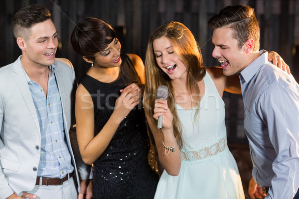 Happy friends singing songs together Stock photo © wavebreak_media