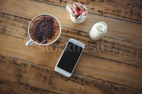 чашку кофе мобильного телефона молоко бутылку таблице древесины Сток-фото © wavebreak_media