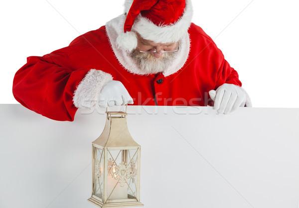 Santa claus holding christmas lantern on white board Stock photo © wavebreak_media