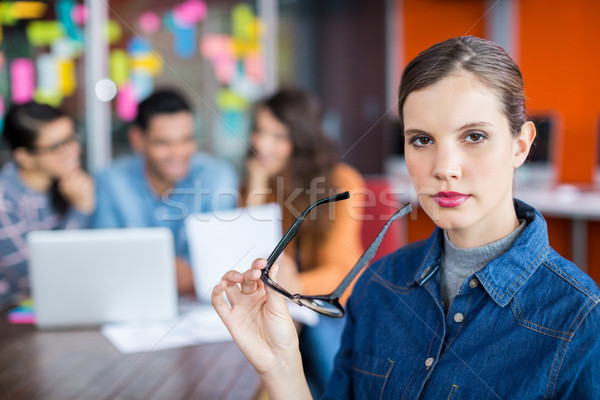 Portrait of female executive standing with spectacles Stock photo © wavebreak_media