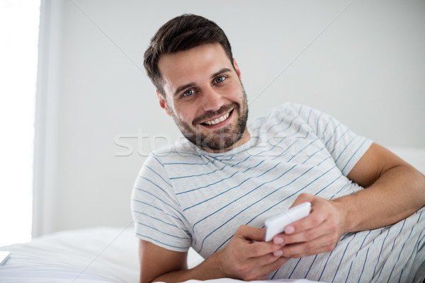 Portrait of man using mobile phone on bed Stock photo © wavebreak_media