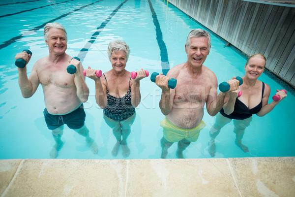 Happy swimmers weightlifting in swimming pool Stock photo © wavebreak_media