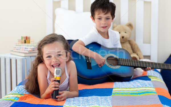 Little boy playing guitar and his sister singing Stock photo © wavebreak_media