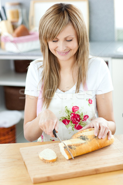 Delighted woman cutting bread in the kitchen Stock photo © wavebreak_media
