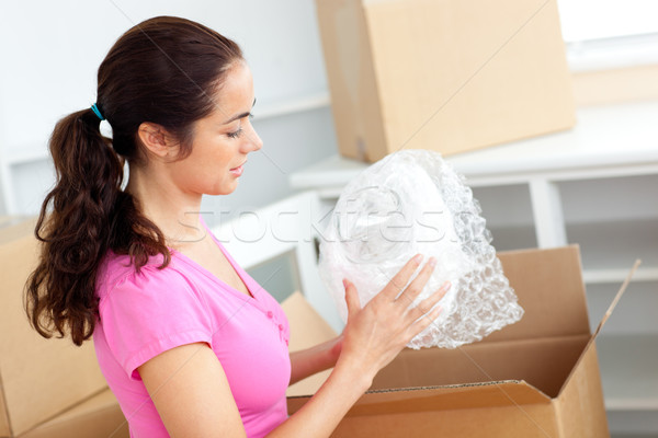 Young caucasian woman unpacking boxes with glasses in her new house Stock photo © wavebreak_media