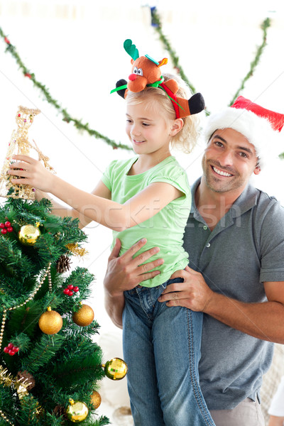 Happy father helping his daughter to put an angel on the Christmas tree Stock photo © wavebreak_media