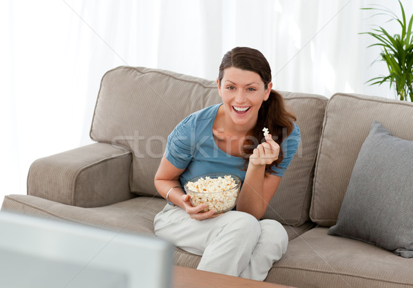 Merry woman eating pop corn while watching a movie on television at home Stock photo © wavebreak_media