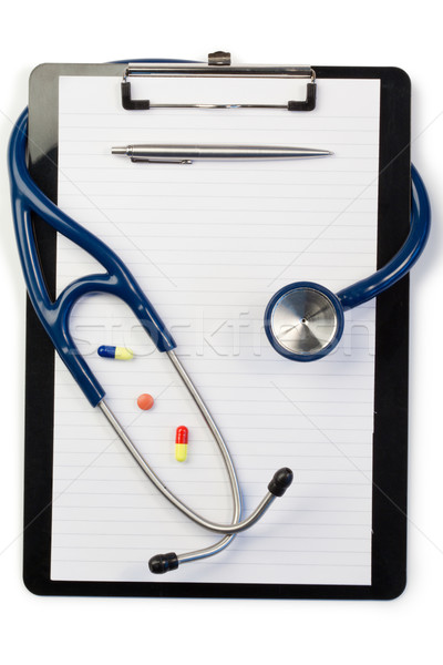 Note pad and stethoscope with pen at the top and pills on a white background Stock photo © wavebreak_media