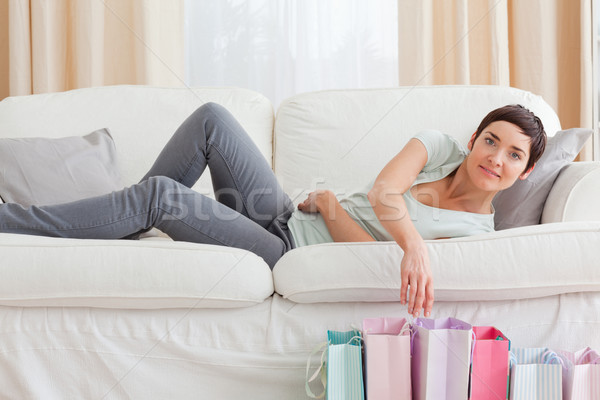 Young woman looking into shopping bags in her living room Stock photo © wavebreak_media