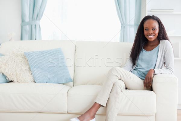 Smiling woman leaning back on sofa Stock photo © wavebreak_media
