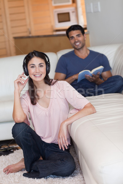 Portrait of a young woman listening to music while her husband is reading a book in their living roo Stock photo © wavebreak_media