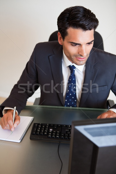 Portrait of a focused businessman taking notes in his office Stock photo © wavebreak_media