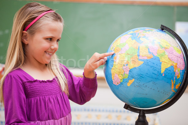 Cute schoolgirl pointing at a country on a globe Stock photo © wavebreak_media