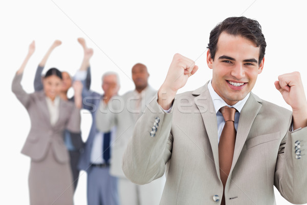 Smiling businessman with team behind him raising fists against a white background Stock photo © wavebreak_media