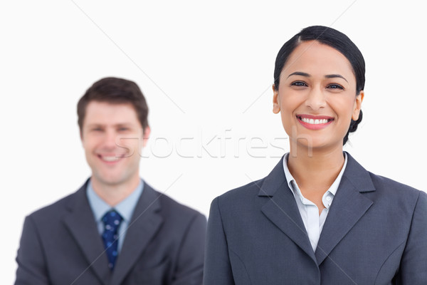 Stock photo: Close up of smiling saleswoman with colleague behind her against a white background