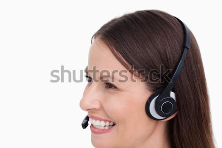 Close up side view of smiling female call center agent against a white background Stock photo © wavebreak_media