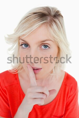 Young fair-haired woman telling to shut up with a finger on mouth Stock photo © wavebreak_media