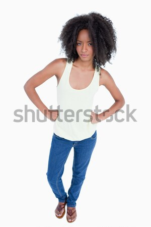 Angry woman placing her fists on her hips against a white background Stock photo © wavebreak_media