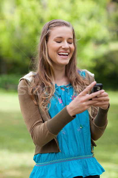 Laughing teenager standing in a park while receiving a text on her mobile phone  Stock photo © wavebreak_media