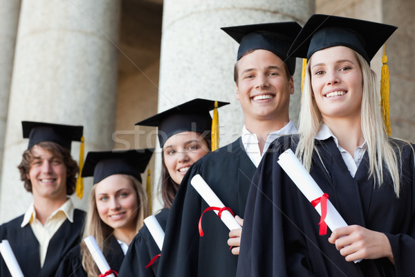 Close-up of five smiling graduates posing in front of the university Stock photo © wavebreak_media