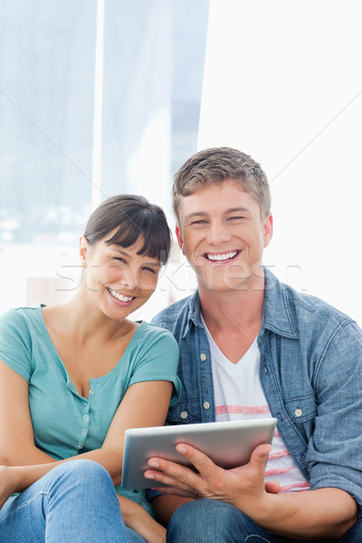 A couple with a tablet pc in their hands smiling as they look into the camera Stock photo © wavebreak_media