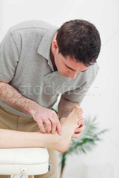 Podiatrist examining the foot of a patient in a room Stock photo © wavebreak_media