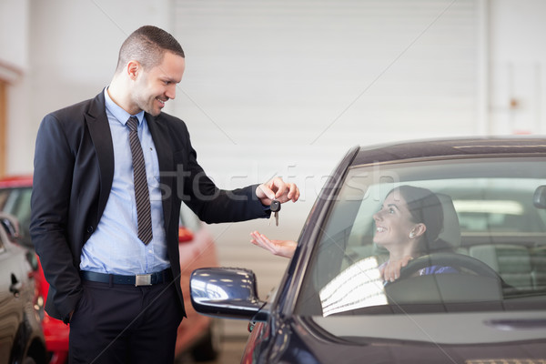 Salesman smiling while giving keys to a woman in a car dealership Stock photo © wavebreak_media
