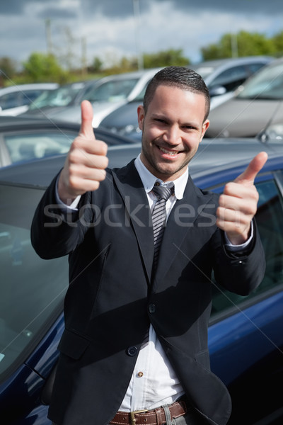 Businessman raising his thumbs while smiling outdoors Stock photo © wavebreak_media