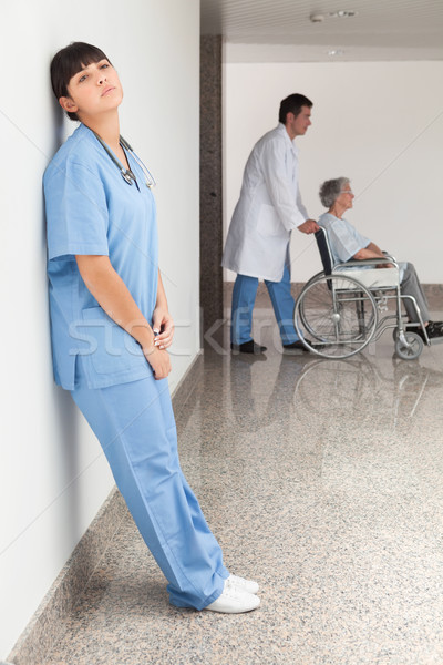 Tired nurse leaning against wall while doctor pushes patient in wheelchair Stock photo © wavebreak_media