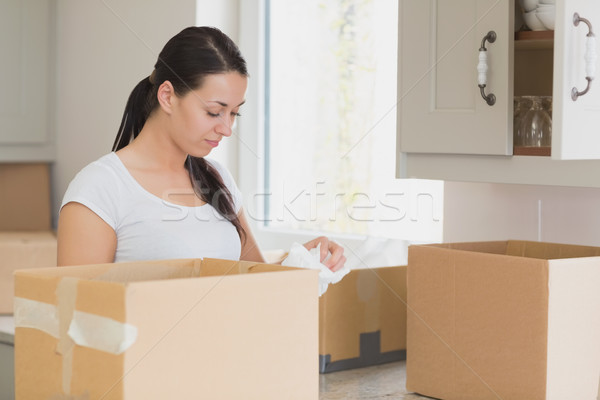 Young woman unpacking in kitchen with many boxes Stock photo © wavebreak_media