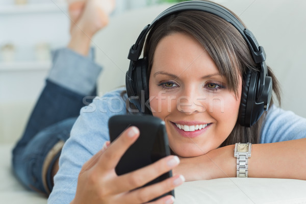 Foto d'archivio: Donna · smartphone · ascoltare · musica · divano · soggiorno · casa