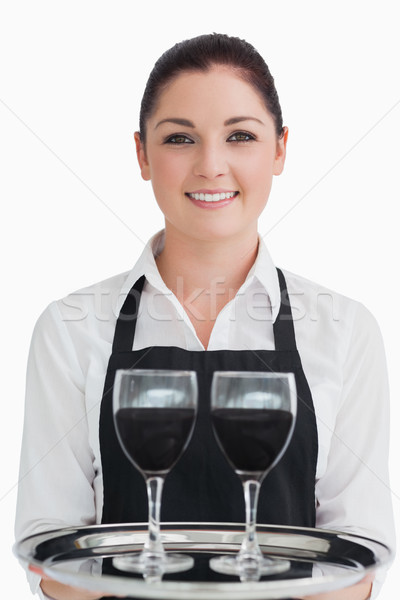 Smiling waitress holding two glasses of red wine on a silver tray  Stock photo © wavebreak_media