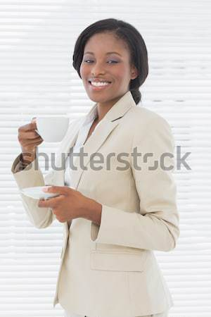 Elegant smiling businesswoman with tea cup in office Stock photo © wavebreak_media