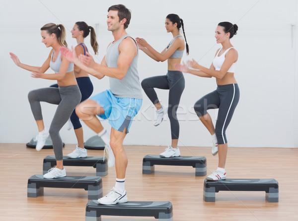 Fitness class performing step aerobics exercise Stock photo © wavebreak_media