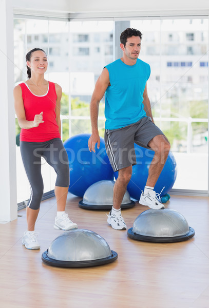Couple performing on dome balance in bright gym Stock photo © wavebreak_media