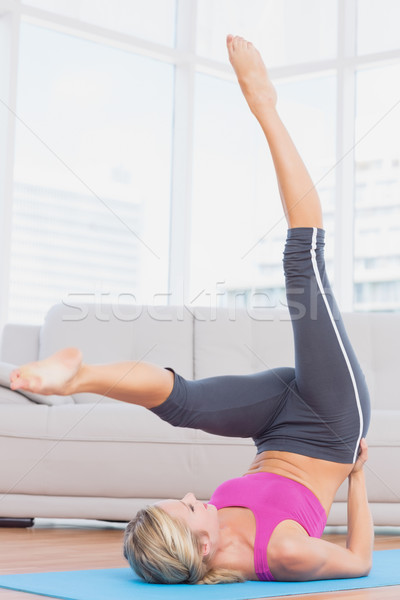 Fit blonde lifting her legs and hips on exercise mat Stock photo © wavebreak_media