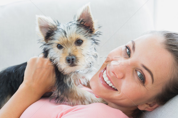 Happy woman cuddling her yorkshire terrier on the couch Stock photo © wavebreak_media