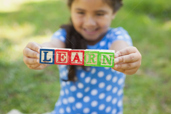 Happy girl holding block alphabets as learn at park Stock photo © wavebreak_media
