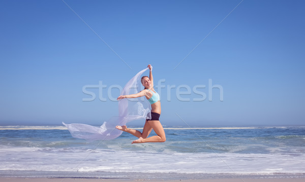 Fit woman jumping gracefully on the beach with scarf Stock photo © wavebreak_media