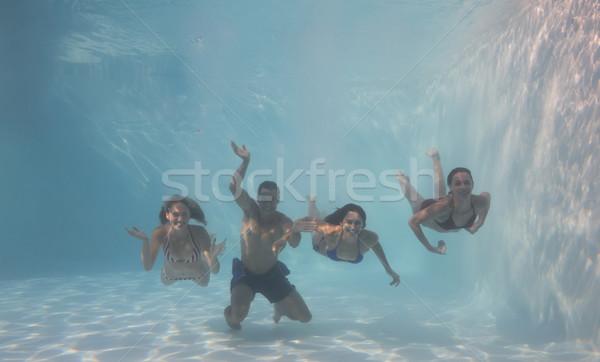 Smiling friends looking at camera underwater in swimming pool Stock photo © wavebreak_media
