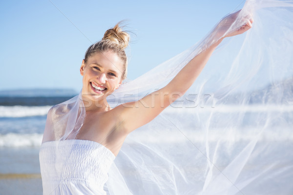 Pretty blonde in white dress holding up shawl on the beach  Stock photo © wavebreak_media