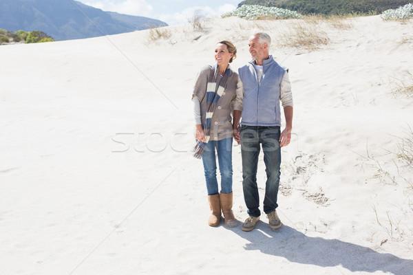 Attractive couple standing holding hands on the beach Stock photo © wavebreak_media