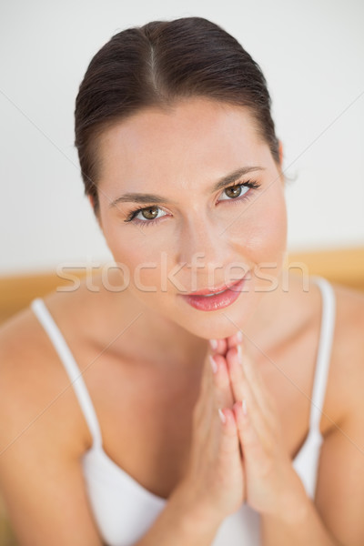 Smiling brunette meditating with hands together Stock photo © wavebreak_media