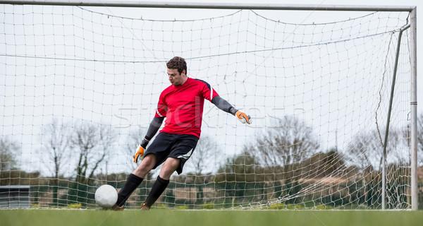 Goalkeeper in red kicking ball away from goal Stock photo © wavebreak_media