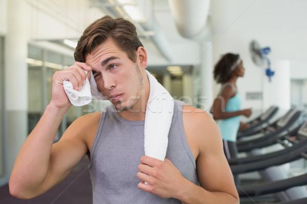 Handsome man wiping his forehead beside treadmills Stock photo © wavebreak_media