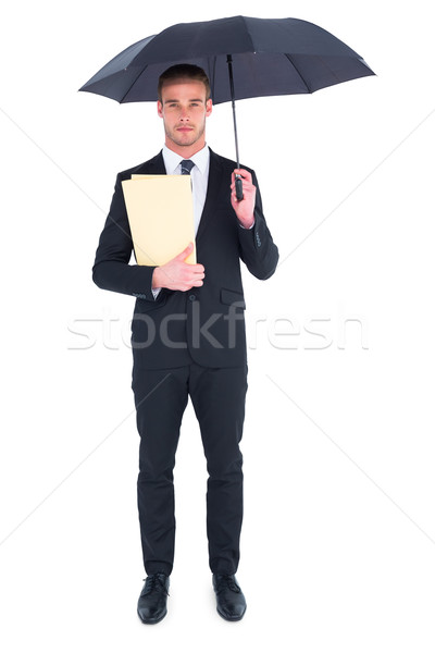 Businessman sheltering under umbrella holding file Stock photo © wavebreak_media