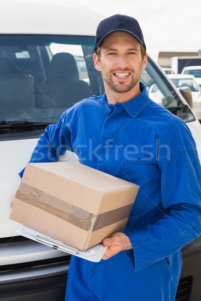 Delivery driver smiling at camera by his van holding parcel Stock photo © wavebreak_media