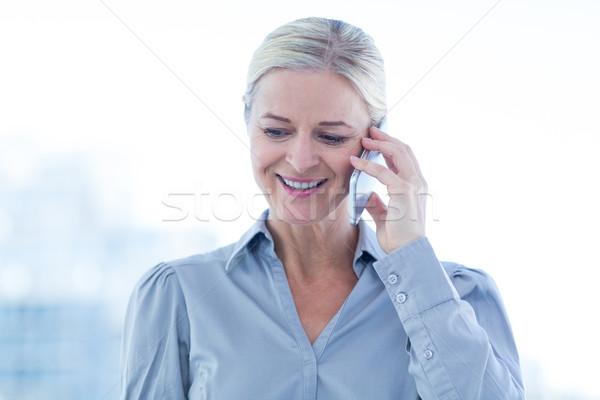 Mosolyog üzletasszony telefonbeszélgetés iroda nő öltöny Stock fotó © wavebreak_media